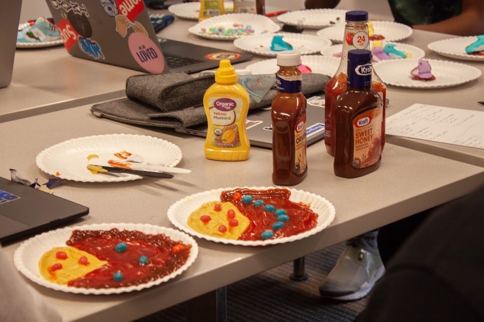 Plates of multicolored condiments rest on a table with bottles of mustard and ketchup.