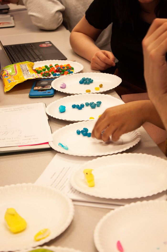 Several plates are arranged on a folding table with multicolored jellybeans on top of each.