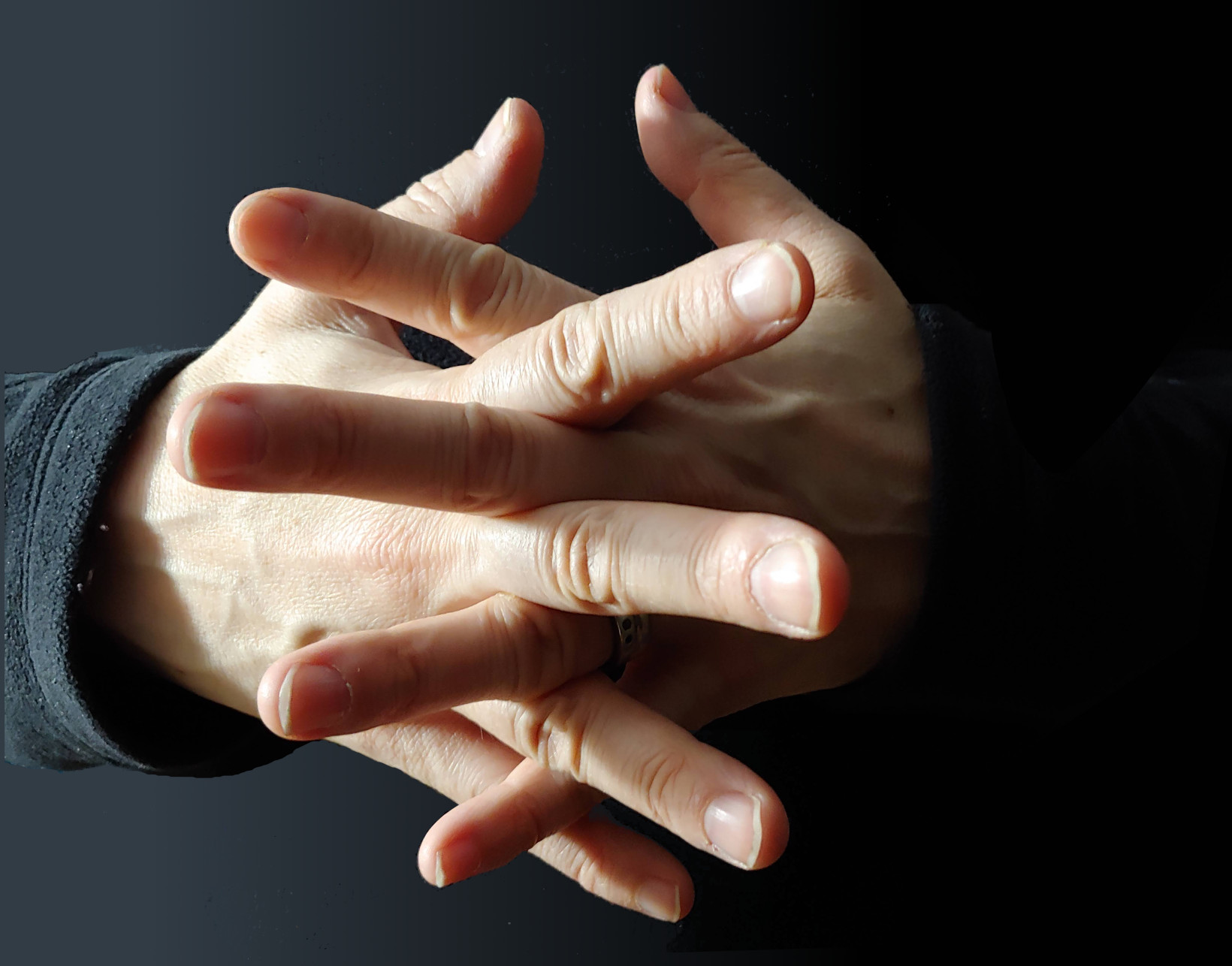 pair of hands with fingers interleaved, at cross angles
