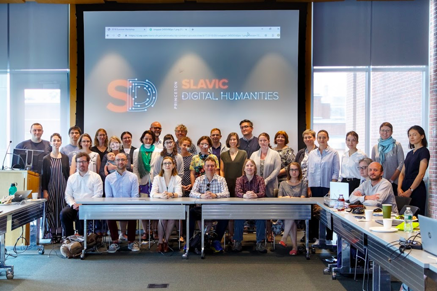 "A group of adults stand in front of a screen reading ""Princeton Slavic Digital Humanities."""